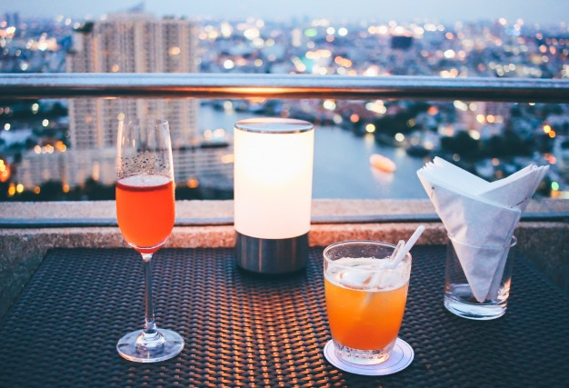 cocktail-glasses-with-candle-light-in-rooftop-bar-against-city-view_Koh Samui Hotels, Samui Beachfront, Chaweng Hotel, First Bungalow, Hotel Samui, rental Samui, booking room, Thailand, full moon party, koh phangan, koh tao samui festival samui event samui wea one day trip samui